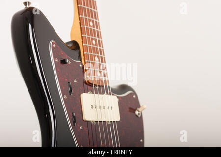 Close up of three controls on black electric guitar, studio shoot. Red tortoise shell pickguard, alder body, two single coil. - Stock Photo
