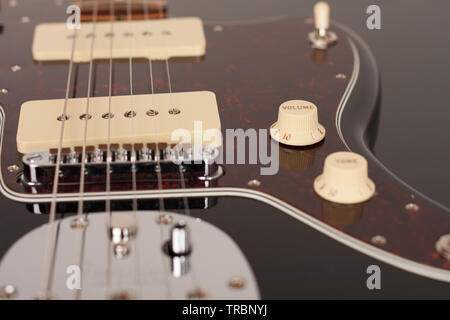 Close up of control volume on black electric guitar, studio shoot. Red tortoise shell pickguard, alder body, two single coil. - Stock Photo