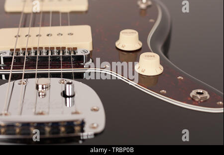Close up of control tone on black electric guitar, studio shoot. Red tortoise shell pickguard, alder body, two single coil. - Stock Photo