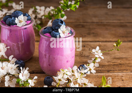 Blueberry yogurt or yoghurt in glasses served with fresh blueberries and spring blossom cherry flowers on rustic wooden table. close up - Stock Photo