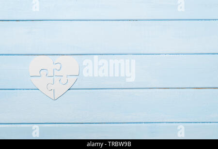 White heart made of symbolic autism puzzle pieces - Stock Photo
