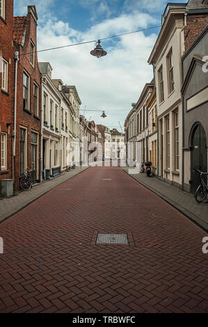 Empty street with brick houses and bicycles in front of doors at s-Hertogenbosch. Gracious historical city with vibrant cultural life in Netherlands. - Stock Photo