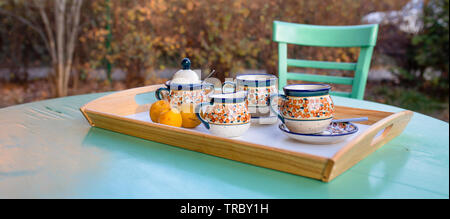 Coffe time, colorful mugs on the green table, Poish  ceramics, pottery. - Stock Photo