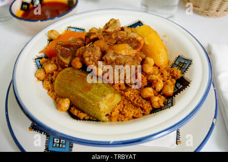 A traditional North African dish of couscous with lamb, chickpeas and vegetables, served at a restaurant in the medina of Tunis, Tunisia. - Stock Photo