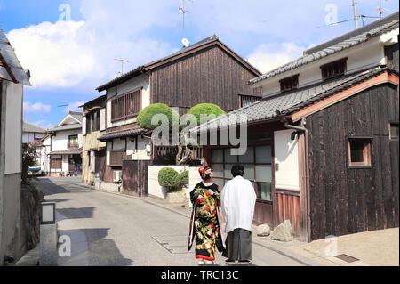 Man and woman in traditional Japanese clothes kimono and hakama walk on medieval street in Bikan district, Kurashiki, Japan - Stock Photo