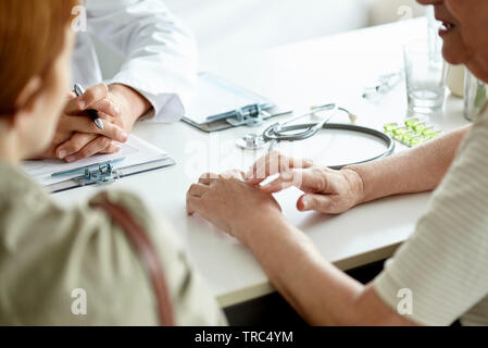 Mother and daughter talking with doctor - Stock Photo