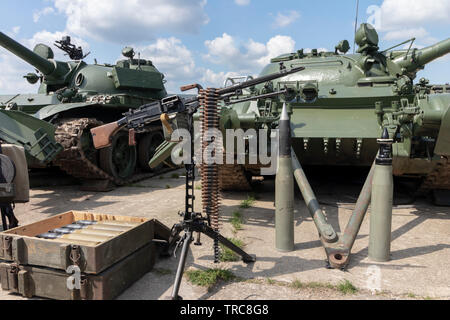 BUDAPEST/HUNGARY - 05.18, 2019: Old Russian weaponry in the field: tank shells in ammo crates, 120 mm rounds placed upwards, heavy machine gun on trip - Stock Photo