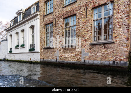 Medieval houses on Groenerei canal sticking right from the water in Bruges, Belgium. Cityscape of Bruges streets shot from the boat. - Stock Photo