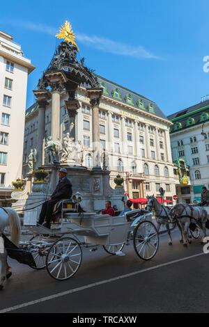 Vienna tourism, view of a horse drawn carriage containing tourists passing the Vermahlungsbrunnen monument in the Old Town area of Vienna, Austria. - Stock Photo