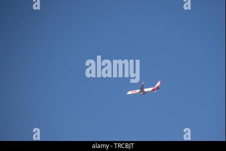 Johannesburg, South Africa - A TAM airliner on an international flight isolated in the sky above the city image with copy space in landscape format - Stock Photo