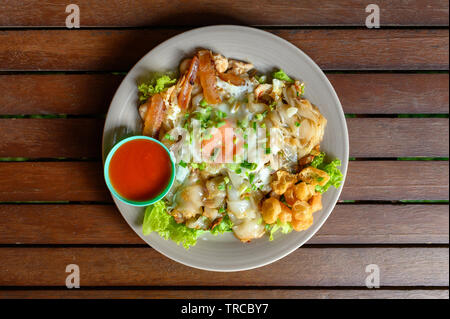 Stir-fried rice noodle with chicken, squid, fry egg and lettuce on plate - Stock Photo