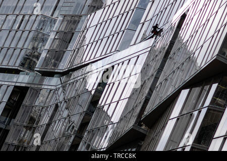 A window cleaner dangles high up on Circus West Village next to Battersea Power Station in south London on May 31, 2019. - Stock Photo