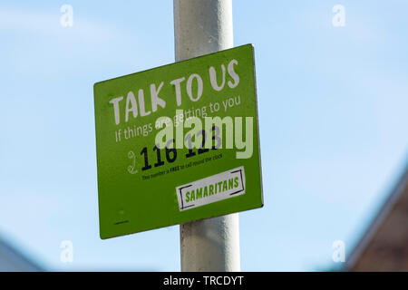 Talk to us if things are getting to you Samaritans sign on post at railway train station at Bournemouth, Dorset UK in June - Stock Photo