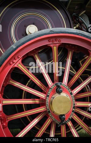 Close-up of the side and large wheel of a red vintage traction engine - Stock Photo