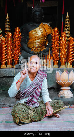 Close-up portrait of a female elderly monk (nun) smiling with one figure pointing up, in front of Buddhist shrine. (Angkor Wat, UNESCO World Heritage - Stock Photo
