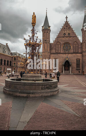 Ornate fountain in front of the gothic Ridderzaal (great hall) at The Hague. Is a mix of historic city with modernity in Netherlands. - Stock Photo