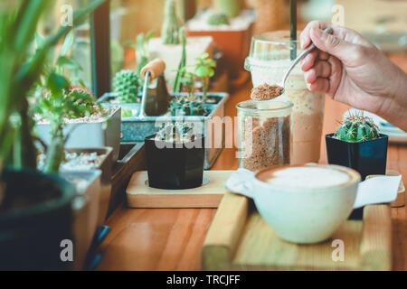 Woman pouring sugar into a white cup of coffee. Selective focus on brown sugar in glass bottle.