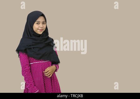 portrait of a beautiful Muslim hijab woman and smiling by posing in front of the camera. Isolated from a white background - Stock Photo
