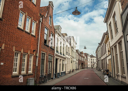 Street with brick houses and bicycles in front of doors in s-Hertogenbosch. Gracious historical city with vibrant cultural life in Netherlands. - Stock Photo