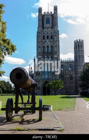Seen in front of the West Tower of Ely Cathedral, the Russian Cannon captured during the Crimean War which was presented to the people of Ely by Queen - Stock Photo