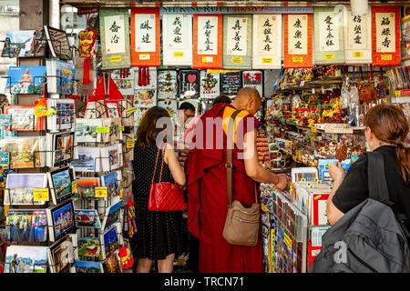A Buddhist Monk Shopping In A Souvenir Shop In Tsim Sha Tsui, Hong Kong, China - Stock Photo