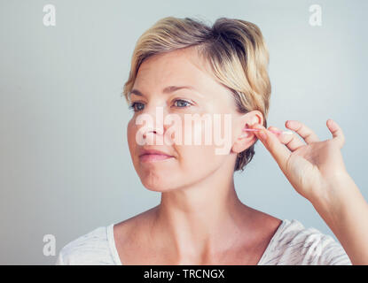 Woman cleans ears with cotton sticks isolated on white - Stock Photo