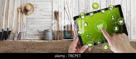 gardening equipment e-commerce concept, online shopping on digital tablet, hand pointing and touch screen with garden tools icons, tool shed in the ba - Stock Photo