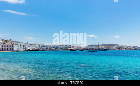 Mykonos, Greece - May 2019: Sailboats and other fishing vessels in the super clear and turquoise waters off the coast of Mykonos Town (Chora) Greece. - Stock Photo