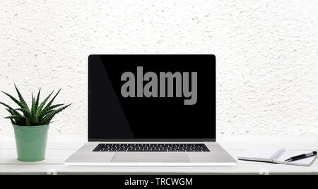 Moder worplace concept - generic silver laptop with a blank screen on a wooden table in the room. - Stock Photo