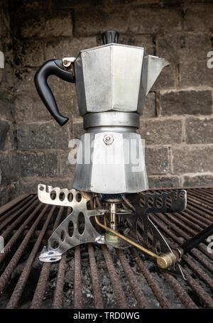 Spanish Cafetera/ Italian Moka coffee maker on camping gas stove. - Stock Photo