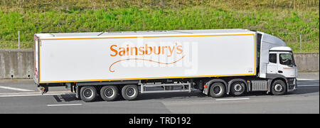 Side view of white hgv Sainsburys supermarket business supply chain delivery lorry truck articulated trailer advertising brand on motorway England UK - Stock Photo