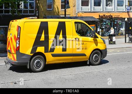 Side & back view of yellow AA breakdown van driving along town centre shopping high street passing Halfords Metro shop in Brentwood Essex England UK - Stock Photo