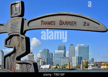 Signpost on riverside towpath to mark the Millennium beside River Thames & forms part of National Cycle network Canary Wharf skyline London England UK - Stock Photo