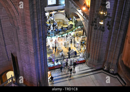Looking down from high above on people shopping in gift shop & cafe inside nave of Liverpool Anglican cathedral with coloured wall lighting England UK - Stock Photo