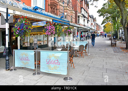 Cafe waits for trade in seaside town shopping street scene old glass canopies & colourful hanging baskets over shop front Lord Street Southport UK - Stock Photo