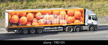 Side view of hgv Sainsburys supermarket business food supply chain delivery lorry truck articulated trailer advertising oranges on motorway England UK - Stock Photo
