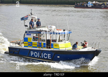 Cameraman filming Met police officer crew aboard Metropolitan Police Marine Policing Unit fast response Targa 31 boat Pool of London River Thames UK - Stock Photo
