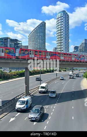 East End high rise skyscraper apartment building towering over train on docklands light railway viaduct above traffic on road Tower Hamlets London UK - Stock Photo