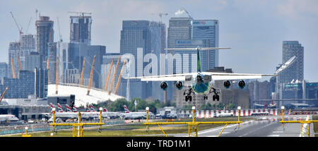 Passenger airplane landing on London City Airport runway Newham O2 arena & Canary Wharf in London Docklands skyline beyond in Tower Hamlets England UK - Stock Photo