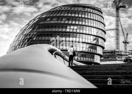 Man standing on the steps of City Hall London - Stock Photo