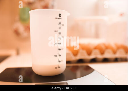 White beaker with milk staying on table scales at kitchen closeup. - Stock Photo