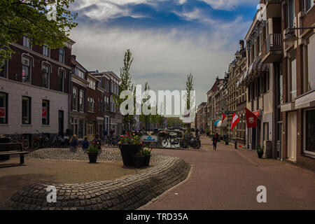 Gouda, Holland, Netherlands, April 23, 2019A little square in Gouda old town, bicycles parked near a bridge in a street of town. Flowers on the backgr - Stock Photo