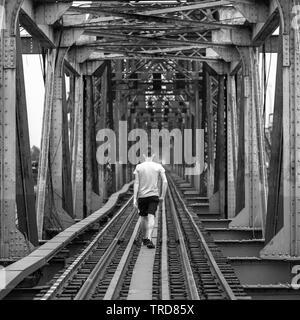Traveler walking on Vintage railway tracks on a tour in Hanoi, Vietnam - Stock Photo