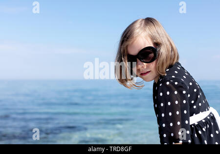 Small (7 years old) pretty cheerful girl in a black  dress with white polka dots is standing on a wooden white pier. Selective focus. - Stock Photo