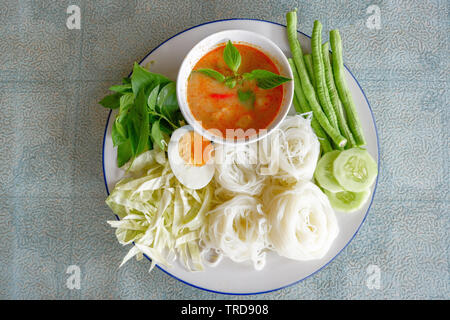 White rice noodle or vermicelli noodle and curry soup sauce on plate with vegetable yardlong , cucumber  bean and egg / Thai style food delicious - Stock Photo