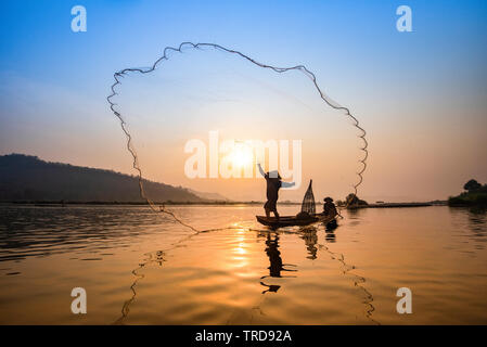 Asia fisherman net using on wooden boat casting net sunset or sunrise in the Mekong river / Silhouette fisherman boat with mountain background people - Stock Photo