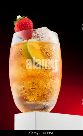 Cocktail with yellow liquid with fruit, strawberry, lime and ice decorations - Stock Photo