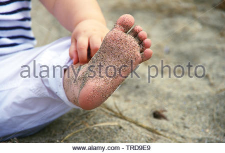 Baby girl wearing white pants & striped shirt, sitting in sand at Kitsilano Beach, Vancouver BC, Canada, stretching out sand-covered foot. - Stock Photo