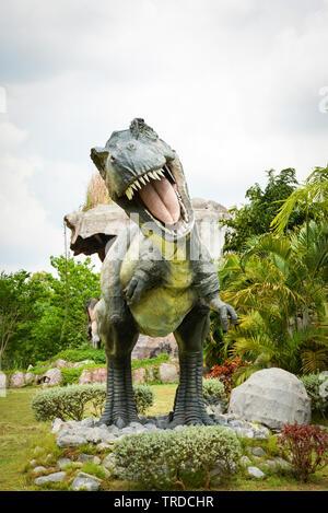 Khon Kaen , Thailand 13 May 2018 : Dinosaur park / different species dinosaur Tyrannosaurus statue T rex in the palm tree garden - Stock Photo