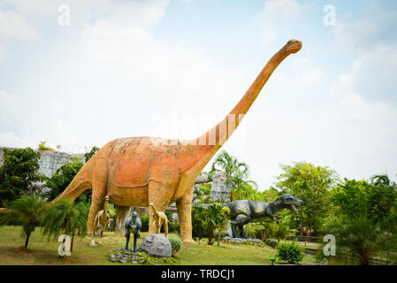 Khon Kaen , Thailand 13 May 2018 : Dinosaur park / different species dinosaur statue in the palm tree garde - Stock Photo